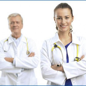 Photo of two doctors standing together, one young and the other ready to retire.